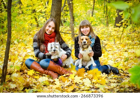 women walking in the park with dogs - stock photo
