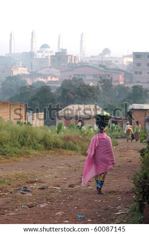 Women walking to the market with goods in Labe with mosque in the background - stock photo