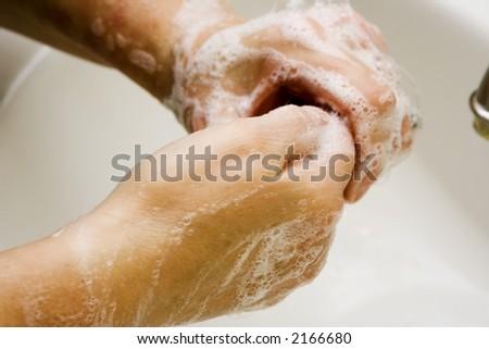 Women washing hands in white sink good suds - stock photo