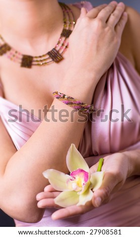 Women wearing evening dress holding a yellow and purple orchid flower in hands. Women only partially visible.