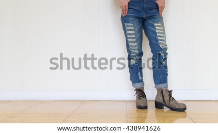 Women wearing jeans and shoes camouflage standing against a white wall.