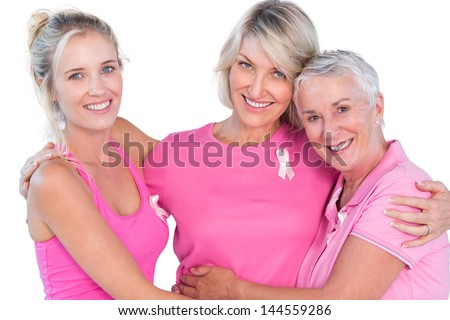 Women wearing pink tops and ribbons for breast cancer on white background - stock photo