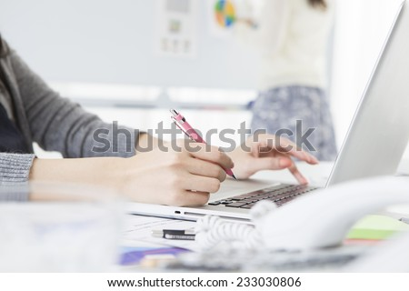 Women who take notes while operating a laptop - stock photo
