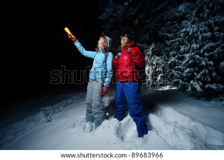 Women with backpacks exploring deep wild forest at night with a torch - stock photo
