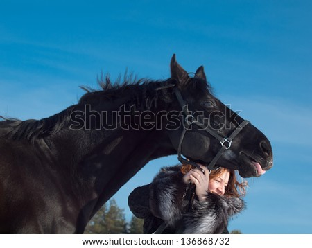 women with black horse at sky background.