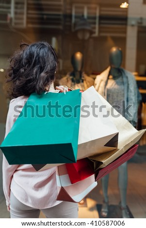 Women with colorful shopping bags looking at boutique showcase - stock photo