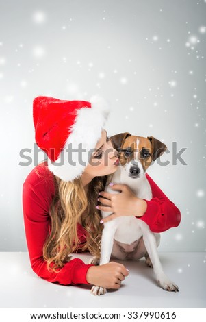 Women with dog in Christmas Santa Hat - stock photo