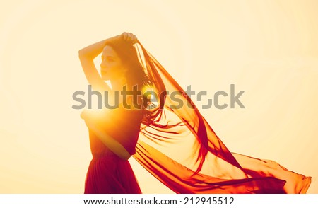 Women with fabric on sunset. - stock photo
