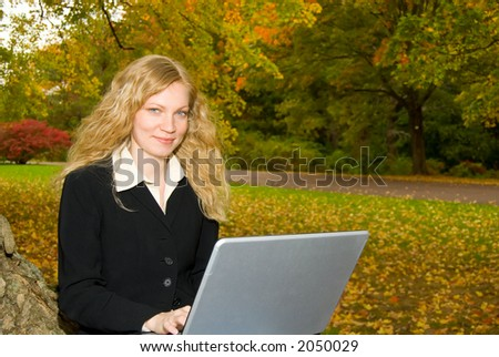 Women with laptop studying in the park in Autumn.
