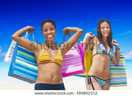Women with shopping bags on a tropical beach. - stock photo