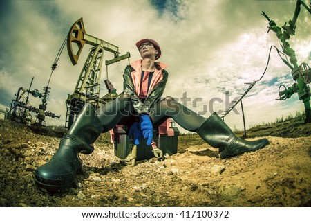 Women worker in the oil field, with wrenches in a hands, orange helmet and work clothes. Industrial site background. Toned.