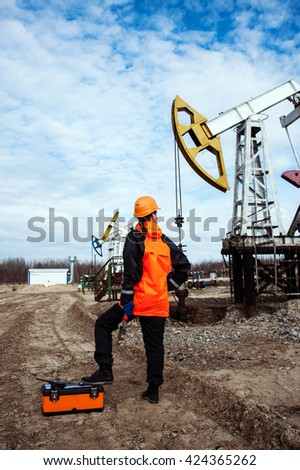 Women worker in the oil field, with wrenches in a hands, orange helmet and work clothes. Industrial site background.