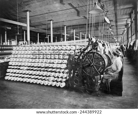 Women working at textile machines, beaming and inspecting yarn, at the American Woolen Company, Boston. The beaming process prepares the warp, the lengthwise fibers of a woven fabric. Ca. 1910. - stock photo