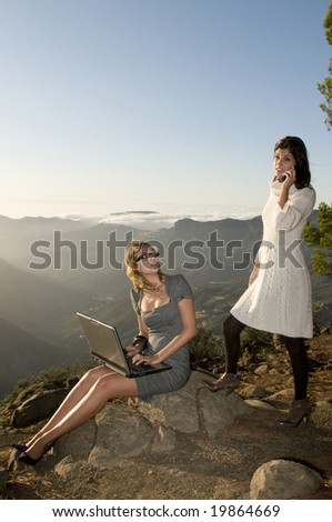 women working with laptop in the mountain and talking by phone - stock photo