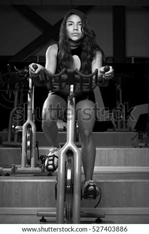 Women workout on bike in gym. Young sexy girl exercise on bicycle black and white colours