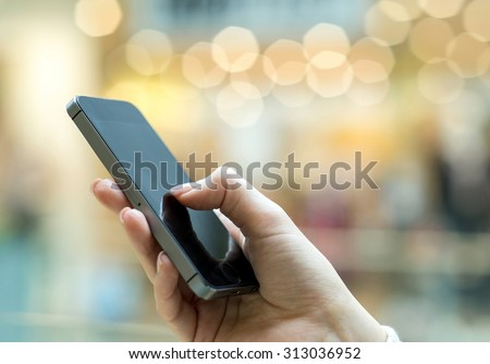 Womens hand using mobile phone on the bokeh background