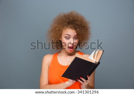 Wondered curly smart surprised young amazed female reading book over gray background - stock photo