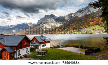 Wonderful Alpine Landscape with green hills, road and Typical Alps Houses, clouds in blue sky. Picturesque panoramic view of nature. Austria, Europe. Awesome alpine highlands in sunny day. Rural Scene