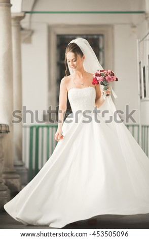 Wonderful bride with a luxurious white dress posing in the old town