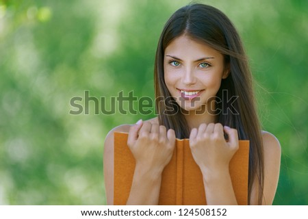 Wonderful dark-haired happy young woman holding an orange book, against background of summer green park. - stock photo