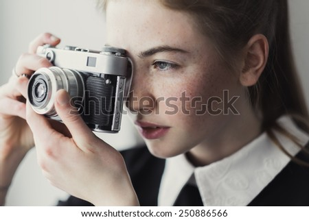 wonderful girl with freckles and vintage camera - stock photo