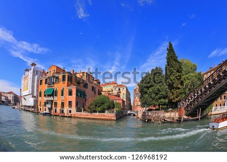 Wonderful holiday in Venice. Ornate facades perfectly restored antique palaces lit setting sun. Graceful bridge spans the Grand Canal.  Photo making the lens Fisheye - stock photo