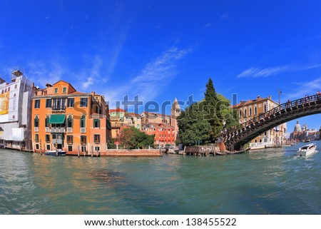 Wonderful holiday in Venice. Ornate facades perfectly restored antique palaces lit setting sun. Graceful bridge spans the Grand Canal. Photo taken by lens Fisheye - stock photo