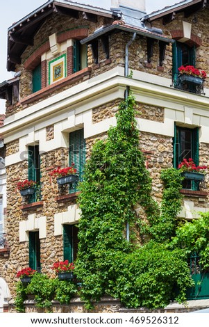 Wonderful picturesque house covered by ivy with geraniums fill boxes on the Montmartre hill, Paris, France