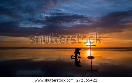 Wonderful reflection on a beach at sunset, with a man kneeling by it. - stock photo