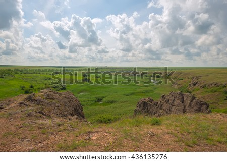 Wonderful scenery - marshy river with steep banks in the prairie. Sunny day in countryside. Ukraine. Toned image. - stock photo