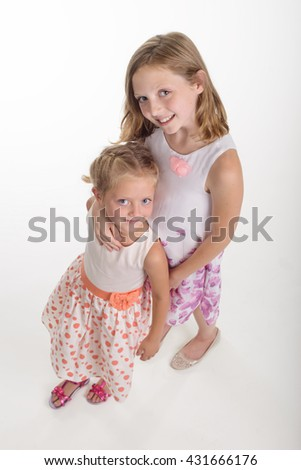 Wonderful siblings with big blue eyes and pleasant smiles. The elder sister embraces the youngest one. Full body shot from the upper angle. - stock photo