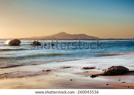Wonderful solar Red Sea beach at a luxury hotel, at sunset. Sharm El Sheikh, Sinai, Egypt. Gold sunset with mountains and big wave. - stock photo