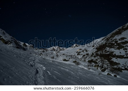 Wonderful starry sky and majestic snowcapped mountain landscape illuminated by the moon soft light. Glowing alpine hut in the distance. Nightscape in the italian Alps. - stock photo