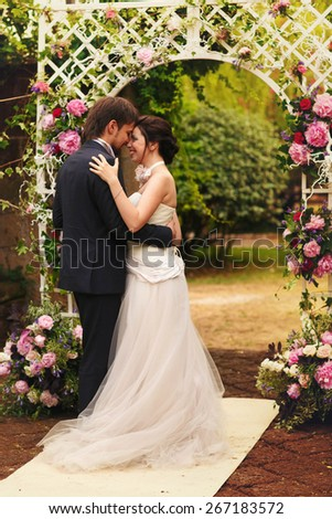 wonderful stylish rich happy bride and groom at a wedding ceremony look at each other in green garden near white arch with flowers Rome Italy  - stock photo