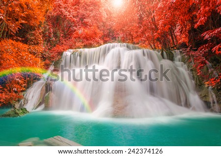 Wonderful Waterfall with rainbows and red leaf in Deep forest at Erawan waterfall National Park, Kanjanaburi Thailand - stock photo