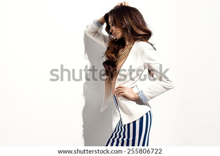 Wonderful young brunette woman in fashionable clothes with long wavy hair. Sensual pose. All white. - stock photo