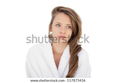Wondering brunette in bathrobe looking away on white background - stock photo
