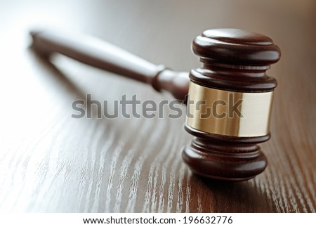 Wood and brass judges gavel standing upright on a wooden desk or table with the handle angled away and focus to the head, shallow dof with copyspace conceptual of judgements and court - stock photo