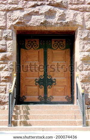 Wood and Wrought Iron Double Doors / Stairs leading up to wooden doors with wrought iron elements, on a pink block building at Graceland Cemetery, Chicago, Illinois, USA
