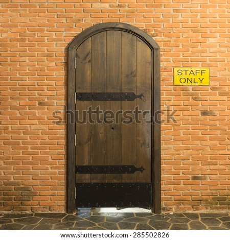 Wood arch door on red brick wall background for staff only - stock photo
