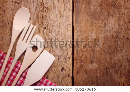 Wood background with copyspace bordered by a red and white country cloth with wooden kitchen utensils lying on top of it - stock photo