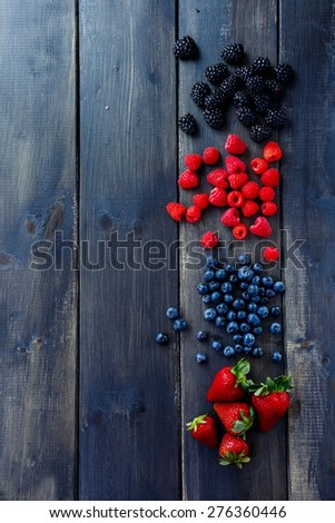 Wood background with Organic spring or summer berries (strawberries, raspberries, blueberries and blackberries). Agriculture, Gardening, Harvest Concept. Top view. Space for text. - stock photo