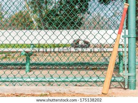 Wood baseball bat leaning on dugout chain link fence. Red bat grip tape on wooden handle. Selective focus on worn bat. Metal player bench, ball, mitt, trees in the blurry background. Horizontal view. - stock photo