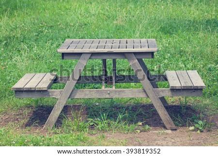 Wood bench at green park in summer season - stock photo