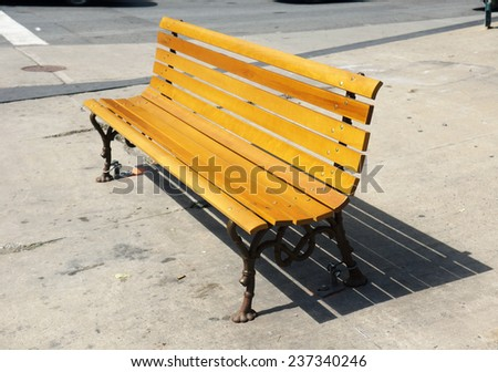 Wood bench on the sidewalk in the city - stock photo