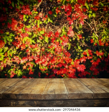 wood board table in front of autumn flowers with double exposure of flower bloom  - stock photo