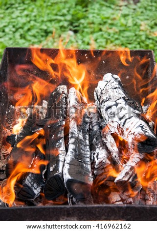 Wood burning in a barbeque grill. Closeup of firewood  - stock photo