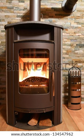 Wood burning stove in front of stonewall - stock photo