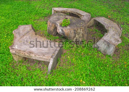 Wood chair made from tree in picnic place in forest - stock photo