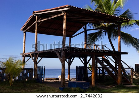 wood construction on tropical beach with blue sky and palms at background